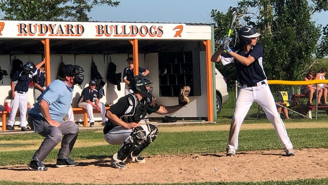 Mackinaw City's Kal O'Brien steps up to the plate, while GFL catcher Jimmy Storey and umpire Tracy Peterson look on in the first game of a doubleheader at Rudyard this past week.