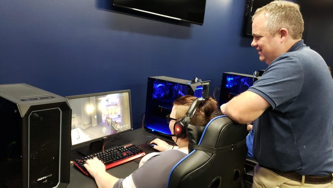 Former Siena Heights esports director and Tecumseh girls soccer coach Thomas Goodman watches Lily Wilson as she plays Overwatch in the Siena Heights Esports Arena in 2018.