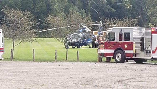 A Life Flight helicopter is pictured at Thompson Memorial Park in Hudson picking up a 6-year-old child who was run over by a reversing pickup Saturday. The child sustained minor injuries.