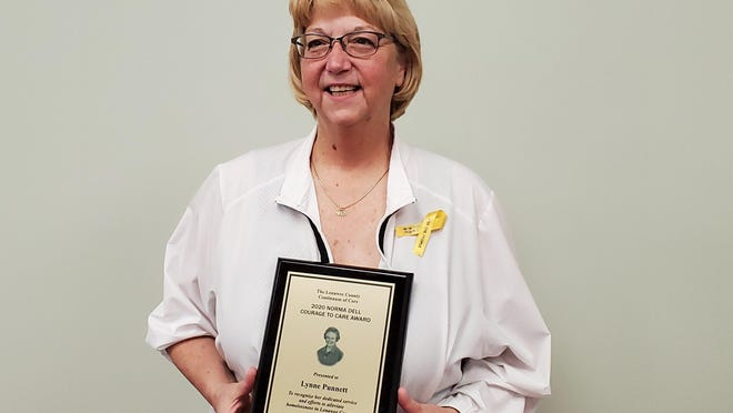 Lynne Punnett, the 2020 recipient of the Normal Dell Courage to Care Award, is pictured with the award after the presentation Tuesday.