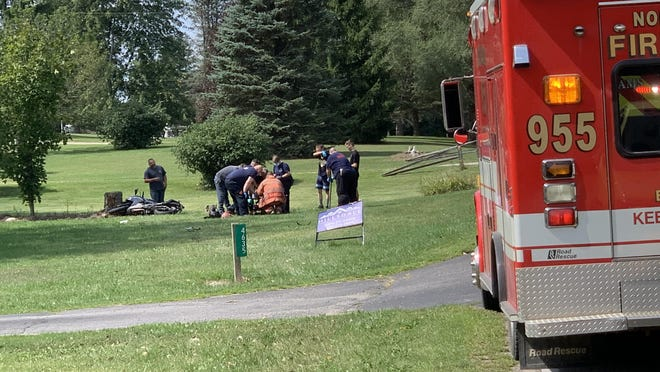 Emergency personnel work to move an injured motorcyclist to the back of a nearby ambulance for transport to Hillsdale Hospital.