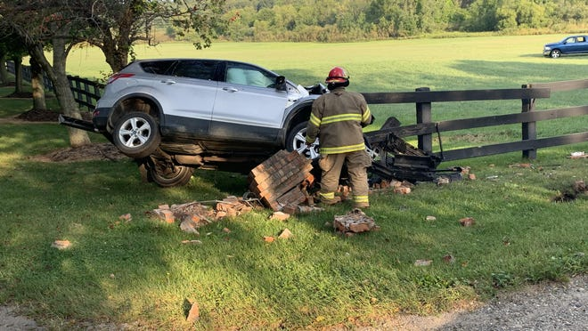 A Hillsdale Township firefighter works the scene of a Tuesday morning SUV/ATV crash.