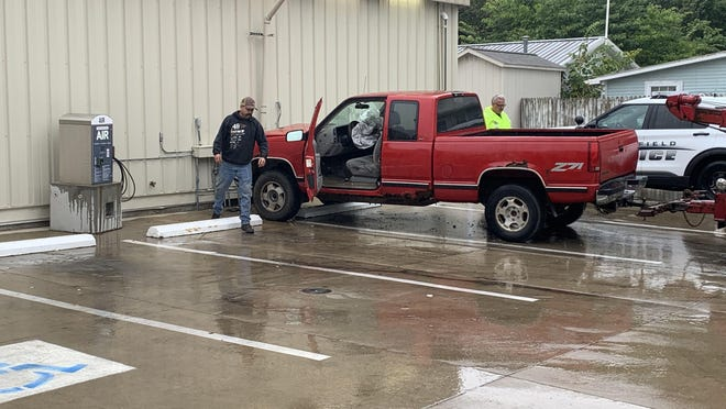A tow-truck operator helps to guide the pickup truck over the curb and away from the Shell Station Monday.