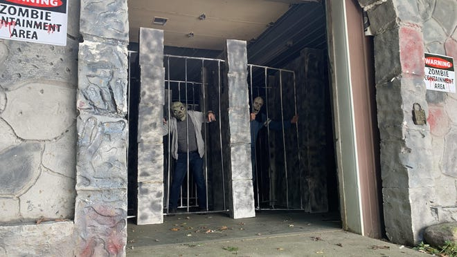 Ray Phillips and an actor work on the Zombie Containment Area on Friday, a few hours before opening.