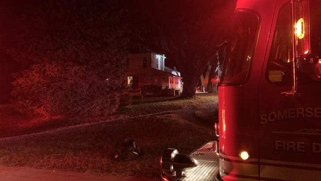 A Somerset fire engine idles at the road as crews work to extinguish a chimney fire Thursday night in Wheatland Township.