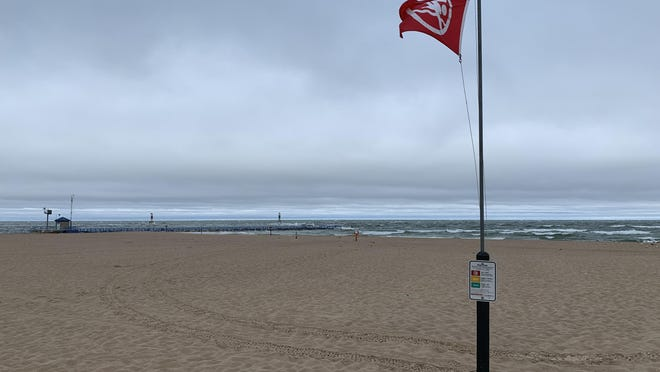 A red flag flies on the beach at Holland State Park. The city of Holland's video team put out a new public service announcement Sunday reminding beachgoers of the dangers of swimming when the red flag is flying, indicating dangerous swim conditions.