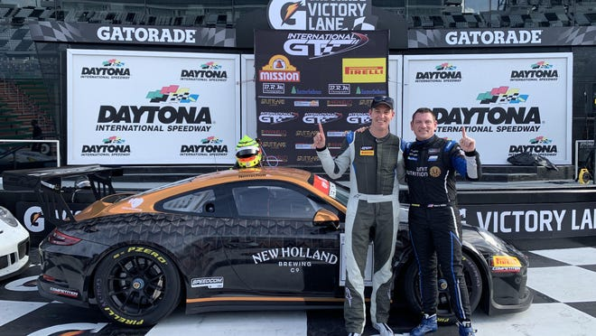 Pail Nemschoff (left) and Marc Miller celebrate their first place overall win at the International GT Enduro Race at Daytona Motor Speedway in the New Holland Brewing Dragon's Milk Porsche.