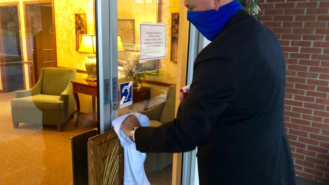 Mike Langeland, funeral director of Ynetma Funeral Home in Zeeland, wipes down the front door with disinfectant after opening, Tuesday, Dec. 22.
