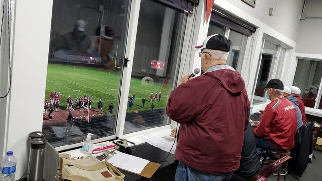 Chuck Minkley stands and announces during a Portland football game.