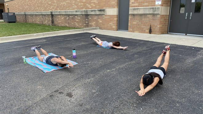 Flat Rock didn't have a pool for many of the first workouts for its new swimming team. Lauren McNamera, Bella Thomas and Sophia Chan worked on their streamlines in the school parking lot.