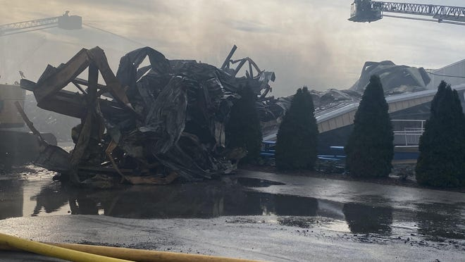 """A collapsed portion of Toledo Beach Marina's """"Rack and Launch"""" building is pictured after Friday's massive fire. About five different companies with excavators worked to tear down parts of the collapsed debris. In the background, firefighters survey the damages."""