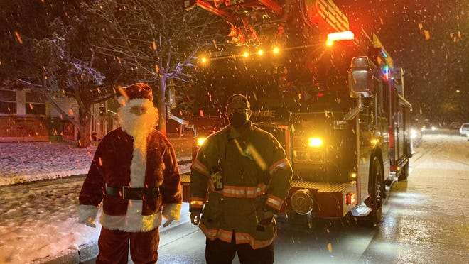"Santa Claus, better known as Manor Elementary School gym teacher Scott Williams, poses with a firefighter from the Monroe Fire Department. Santa led the ""Very Merry Bobcat Parade"" from a city firetruck Thursday night."