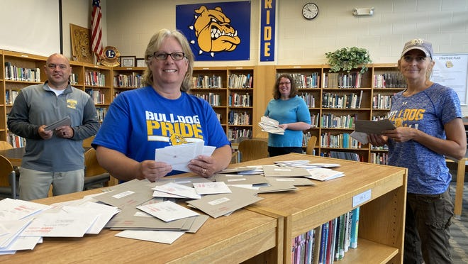 Centreville High School principal Chad Brady and staff members Nancy Griffin, Valerie Roe and Kim Spencer have been addressing envelopes containing letters from class of 1975 alumni written to the school's class of 2020.