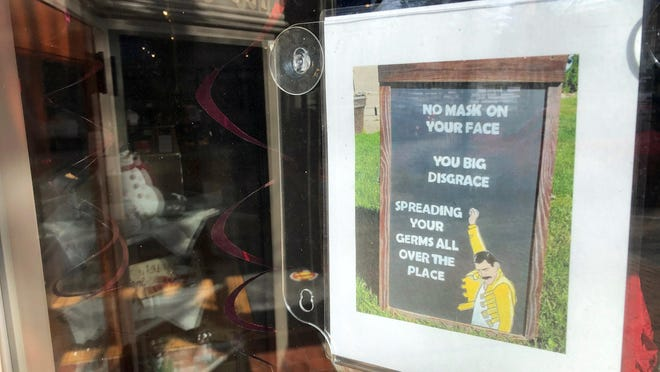 A sign in the front window of Crane's in the City in Holland, Mich., on Monday encourages the public to wear masks.