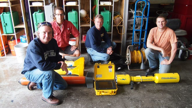 Greg Cook, Ben Wells, Fritz Sharar and Stewart Hood with sonar equipment used to help locate wreckage from a downed military helicopter.