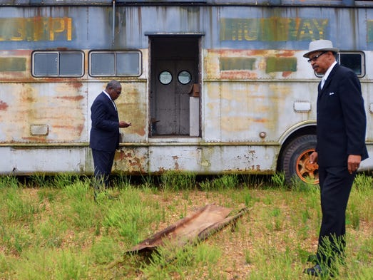State Seantor John Horhn (left) looks over the exterior of a former Highway Patrol vehicle that vintage car and film collector Johnny Morrow (right) says was used at Jackson State University in 1970 shootings that killed two students and injured 12 others. The vehicle is being stored at the old Mid-State Auction facility on N. State Street in Jackson.