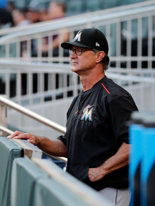 Miami Marlins manager Don Mattingly (8) looks out from the dugout before a baseball game against the Atlanta Braves, Saturday, Aug. 5, 2017, in Atlanta. (AP Photo/John Bazemore)