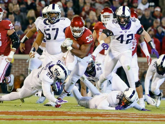 FILE - In this Saturday, Nov. 21, 2015, file photo, Oklahoma running back Samaje Perine (32) carries between TCU safety Derrick Kindred (26) and TCU safety Nick Orr (18) during the first quarter of an NCAA college football game in Norman, Okla. Oklahoma plays Oklahoma State on Saturday, Nov. 28. (AP Photo/Alonzo Adams, File)