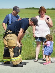 Burkburnett Fire Department first responders talk with a little girl after giving her a stuffed teddy bear. She was one of four occupants in a Jeep SUV that rolled over in an accident on FM 1177. There were no serious injuries in the one-vehicle crash.
