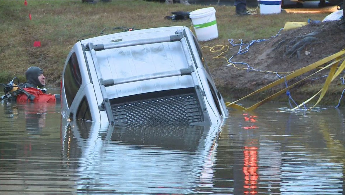 Crews pull a car from a Cherokee County pond