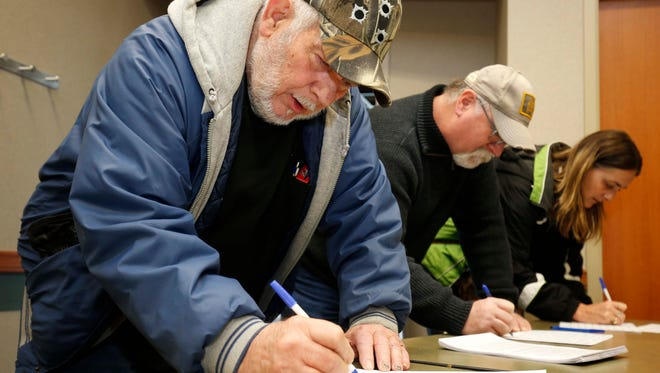 Green County resident Charles Allen signs a petition duirng a training session for petition gatherers at the Library Station in north Springfield on December 30, 2017.