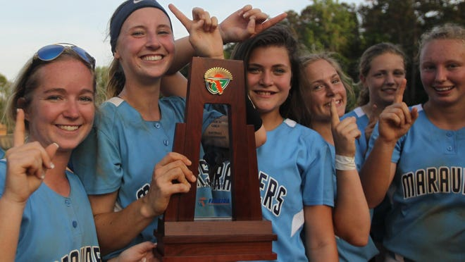 Maclay junior pitcher Kenzie Mullins holds the District 1-3A championship trophy with her teammates after the Marauders won a 9-7 game against NFC to snap a 24-game losing streak to their rivals.