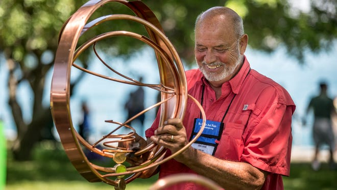 Artist Jim Cook, of Fremont, puts together a copper kinetic lawn sculpture during the St. Clair Art Fair Saturday, June 25, 2016 in St. Clair.