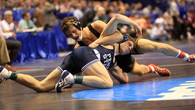 Iowa's Thomas Gilman wrestles Penn State's Jordan Conaway at 125 pounds during the second round of the NCAA Championships in St. Louis on Thursday. Gilman won in overtime, 3-1.