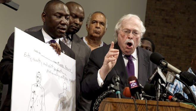 Dr. Michael Baden, right, speaks as Brown family attorney Benjamin Crump, left, holds a diagram produced during a second autopsy done on 18-year-old Michael Brown Monday, Aug. 18, 2014, in St. Louis County, Mo.