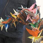 First Christian Church pastor Daniel Mallipudi holds a string of origami cranes displayed at the Roseburg church.