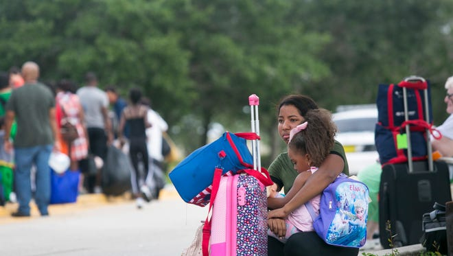 Ashly Saldana, 16, holds her little sister Yasily Rivera, 4, while waiting to get into Germain Arena on Saturday before Hurricane Irma.