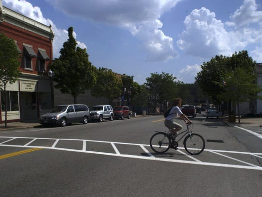 File photo: A bicyclist crosses Route 259 or Main St as it runs through the village of Spencerport.