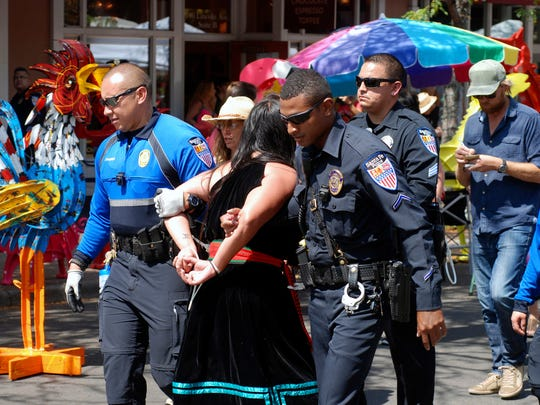 Police in Santa Fe, N.M., lead away protester organizer Jennifer Marley of San Ildefonso Pueblo in hand restraints on Friday, Sept. 8, 2017. Santa Fe police say they arrested at least 12 people to contain protest against an annual pageant marking the return of Spanish conquistador Don Diego de Vargas to New Mexico following a 17th century Indian revolt. Public statues and tributes to early Spanish conquerors are facing mounting criticism tied to the brutal treatment of American Indians centuries ago by Spanish soldiers and missionaries, with activists drawing ethical parallels to the national controversy over Confederate monuments.