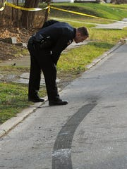 An officer investigates the scene of a shooting in the 500 block of North Johns Ave. Saturday.