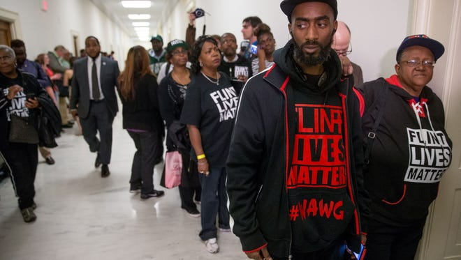 "Flint residents and supporters wear shirts that reads ""Flint Lives Matter"" as they wait outside the room where Michigan Gov. Rick Snyder and EPA Administrator Gina McCarthy testify before a House Oversight and Government Reform Committee hearing in Washington, Thursday, March 17, 2016, to look into the circumstances surrounding high levels of lead found in many residents' tap water in Flint, Michigan."