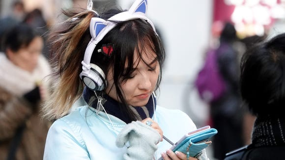 A woman in cat headphones makes notes on her smartphone