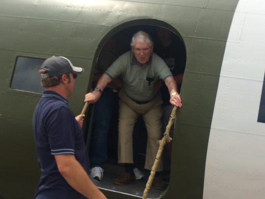 Melvin Breede, a WWII pilot, is helped off a WWII-era plane on Memorial Day when a local businessman and political candidate hosted free flights for veterans in several historic planes.