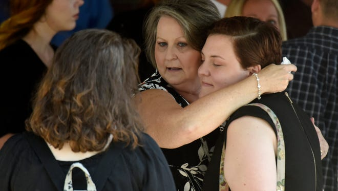 Mourners hug following the funeral for Melanie Crow at West Harpeth Funeral Home & Crematory Thursday, Sept. 28, 2017, in Nashville, Tenn. The 38-year-old mother of two  died Sunday after a shooting at Burnette Chapel Church of Christ.