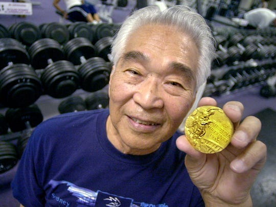 Tommy Kono, shown here in 2002, holds the Olympic gold