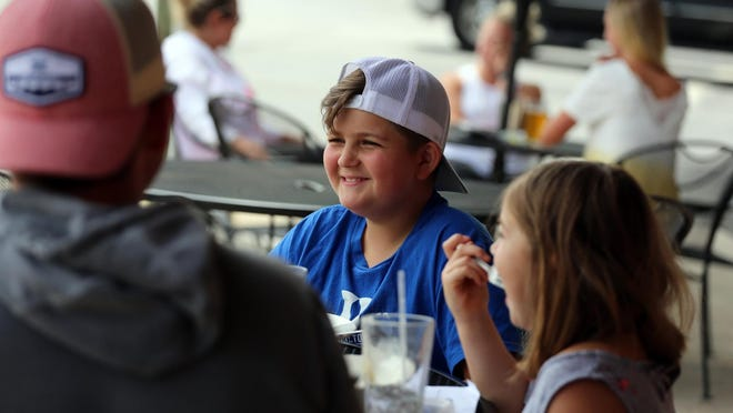August Terry, 11, enjoys lunch with dad Josh and sister Maddie, 7, on the patio at Pleasant City Wood Fired Grille on Friday.