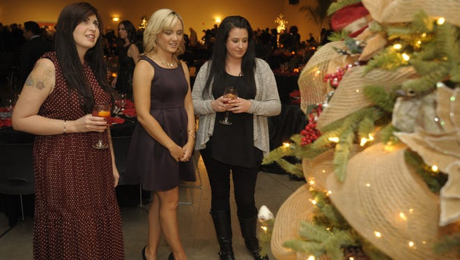 """Tania Gomez, left, Lauren Ferreira, and Jenna Hill look at """"We Give a Hoot"""" tree, decorated by the Bank of the Sierra staff, during the Tulare Hospital Foundation's 2015 Festival of Trees at the Heritage Complex, Tulare."""