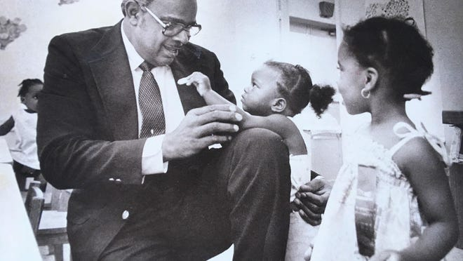 The Rev. C.S. Hamilton is offered a cookie by Tyann Grant while Denika Thomas looks on.