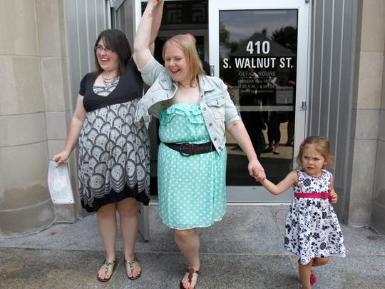 Heather, left, and Natalie Starr with daughter Libby raise their hands in celebration after being married on the steps of the Outagamie County administration building Monday in Appleton. They are the first same-sex couple to be married in the county. Wm.Glasheen/Gannett Wisconsin Media