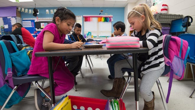 First graders Briceida Niz Sanitzo, left and Kate Donaway works in their desk at North Georgetown Elementary School in Georgetown. The Indian River School District is hosting a current expense referendum to seek additional local funding.
