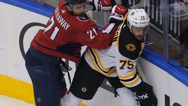 Bruins defenseman Connor Clifton, in his first game action of the postseason, tries to move the puck along the boards while being checked by the Capitals' Garnet Hathaway during Sunday's game.