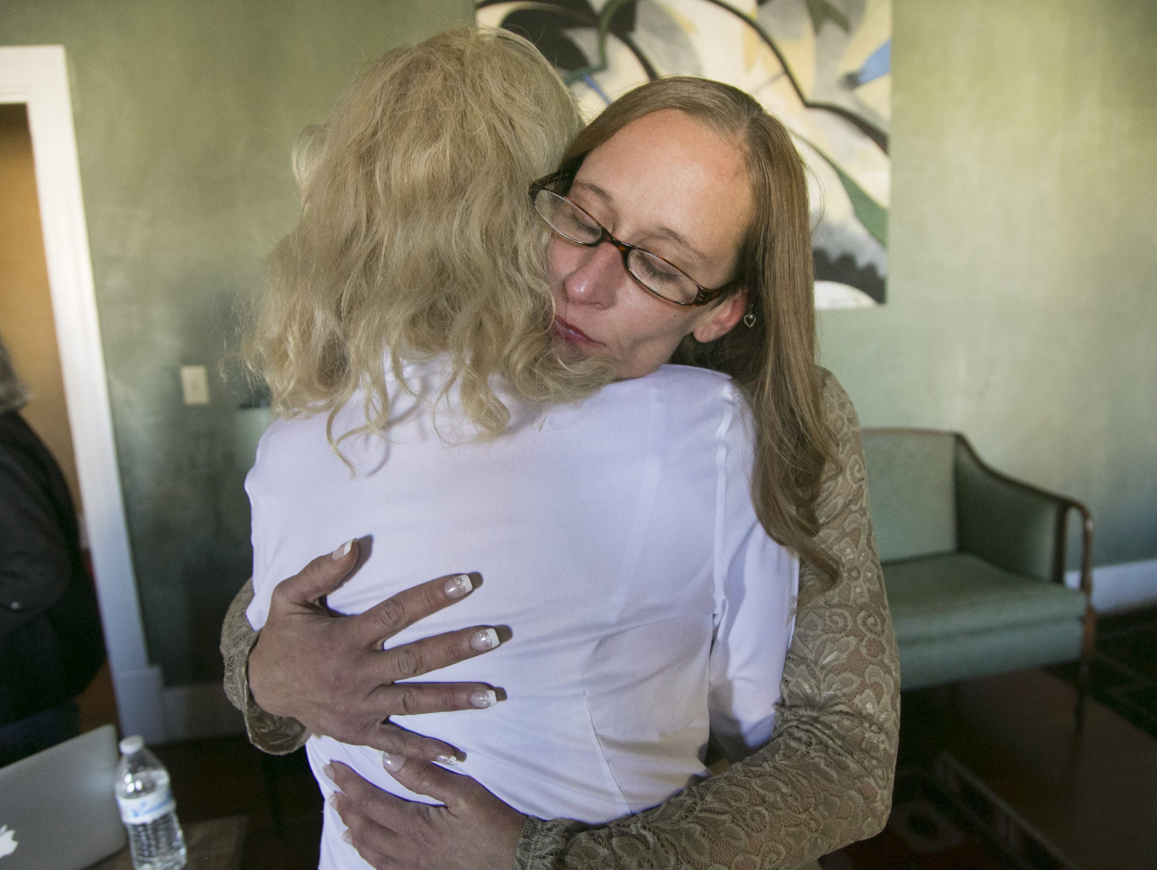 Michelle Calderon (right), of Tucson, hugs her attorney,