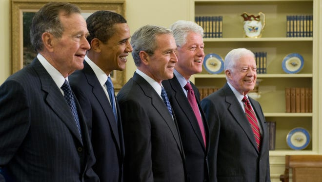 US President George W. Bush (C) stands with President-elect Barack Obama (2nd L), former President George H.W. Bush (L), former President Bill Clinton (2nd R) and former President Jimmy Carter (R) in the Oval Office of the White House in Washington, DC, on January 7, 2009.