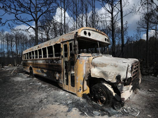 A burnt out school bus, one of multiple vehicles left
