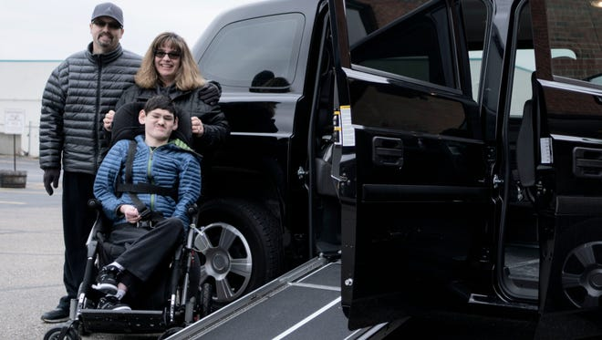 From left: Marc, Sandra and Jordan McKenzie, 13, stand next to their new Mobility Ventures MV-1vehicle on Saturday, Mar. 26, 2016, in Redford.
