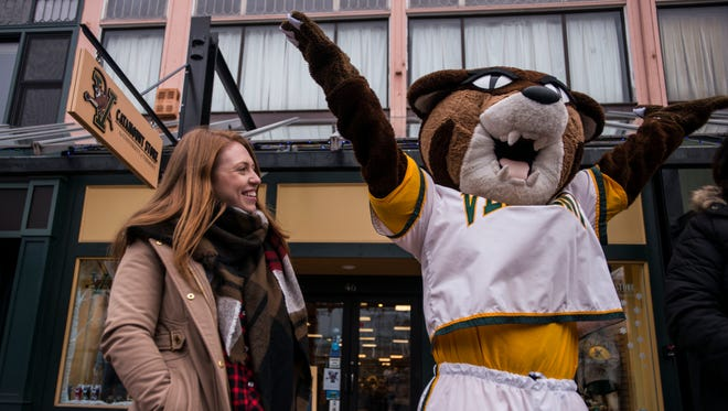 Sculpture Alison Brown watches Rally, the University of Vermont mascot, react to an announcement on Church Street outside of the Catamount Store of a campaign to privately raise $100,000 for a statue of the UVM character to be displayed outside the store.